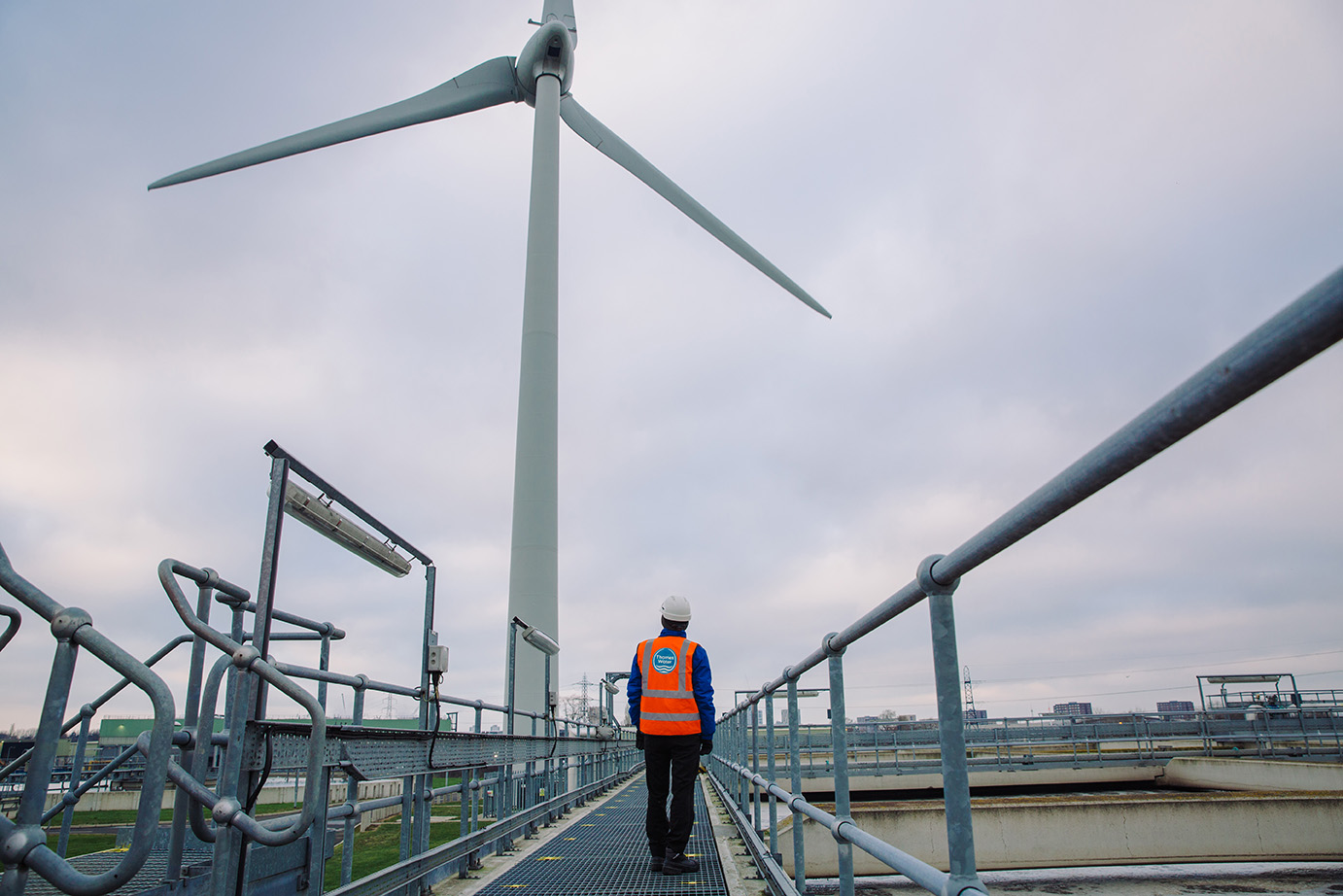 A man in a orange hi-vis looks at a wind turbine