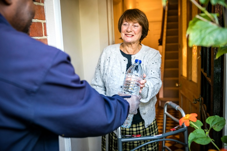 A man in a blue jacket delivers water to an elderly lady with a zimmer frame